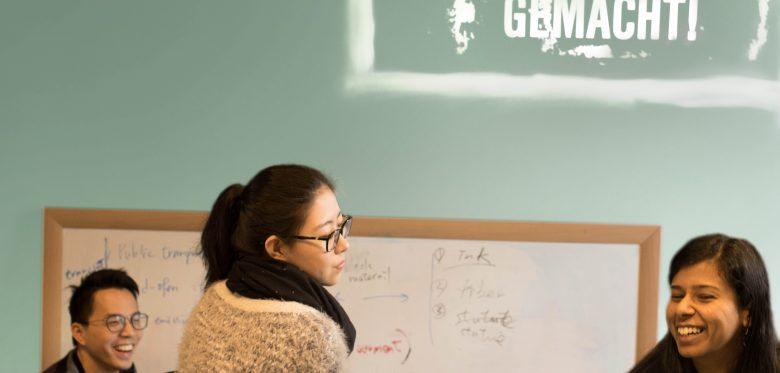 Junge Menschen aus unterschiedlichen Kulturen vor einem Whiteboard