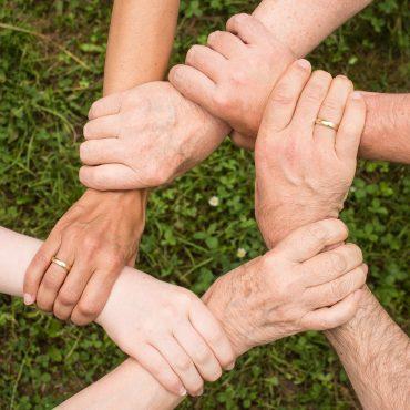 Sechs Hände die sich gegenseitig halten