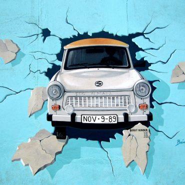 Graffiti von einem Trabbi, der durch die Mauer bricht