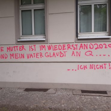 Rotes Graffito vor grauer Hauswand